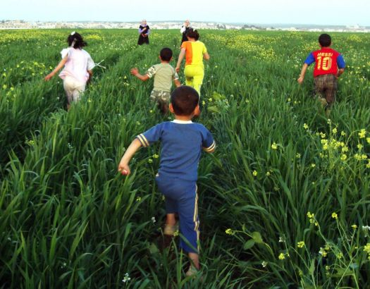 children run through a green field in Jordan