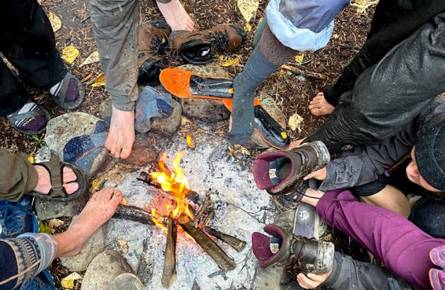 Students warm their feet and dry their boots around a campfire