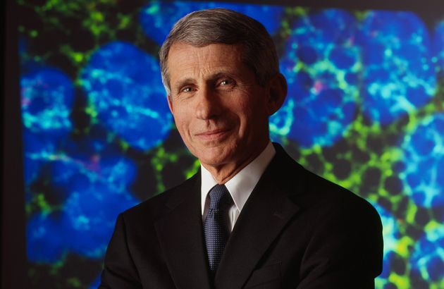 Dr. Anthony Fauci stands facing the camera with his arms crosssed