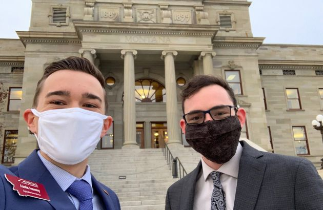 Two UM students wearing masks stand outside the Montana capital building
