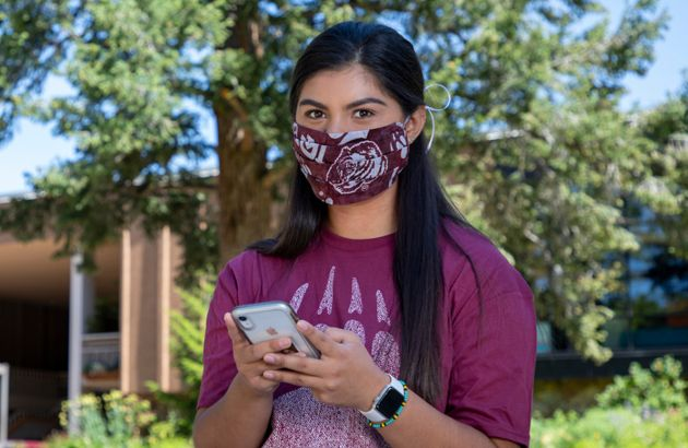 Female student wearing a cloth face covering holds her phone while standing in front of the UC