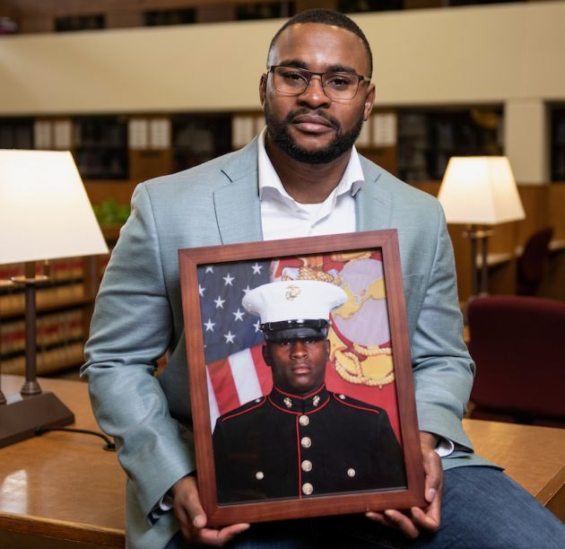 Jacob Elder in the Law library holding photo of himself as a Marine