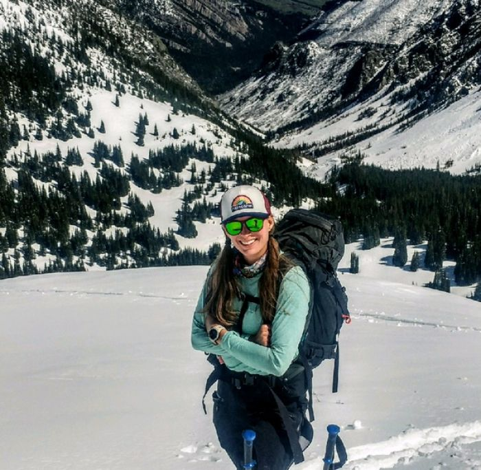 Kirsten Gerbatsch stands in a snowy field with her arms crossed as she smiles and looks at the camera. Two ski poles are visible in front of her.