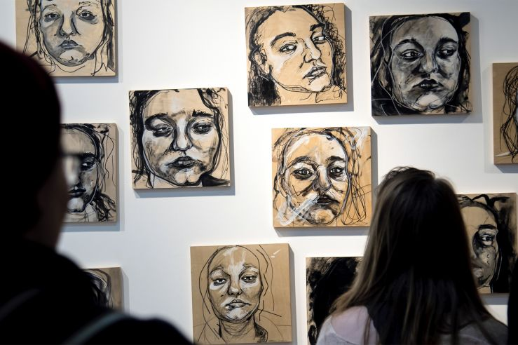 People observing portraits on a UC Gallery wall