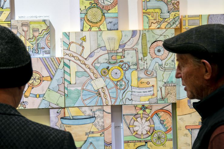 Two men admiring some intricate and colorful Dr. Seuss-like drawings