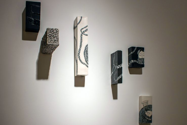 Dramatic shot of some rectangular, 3D mixed media pieces of art protruding from the wall