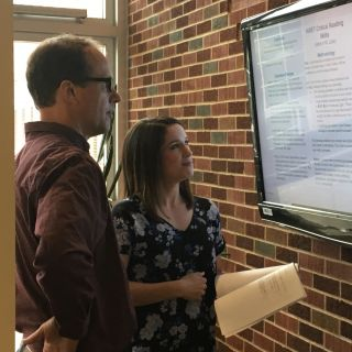 A faculty member and a student look at a text on a screen