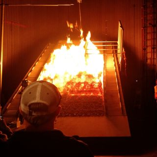 Students look at the burn chamber at the Missoula Fire Lab, a leading federal research facility