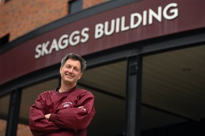 A male stands with arms folded, wearing a Griz shirt and smiling in front of Skaggs Building facade