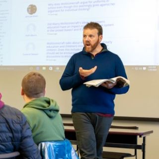 A faculty member delivers a lecture to students
