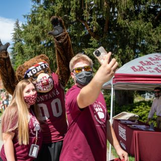 Two students wear masks and take a selfie with UM mascot Monty