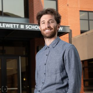 UM law student Noah Goldberg-Jaffe stands in front of the Alexander Blewett III School of Law building and smiles are the camera.