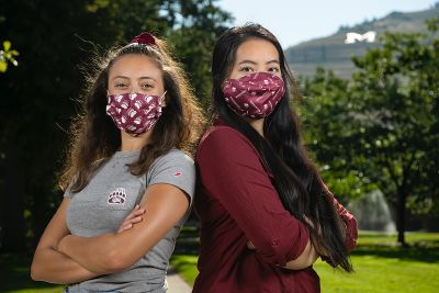 Two female UM students pose for picture with masks