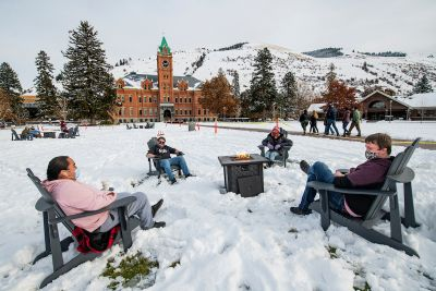 UM students sit around a firepit on the UM campus.