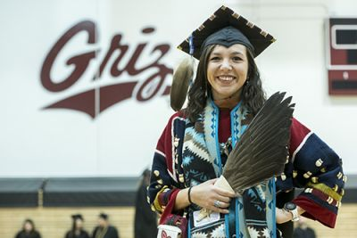 Rose Bear Don't Walk stands before the camera in her graduation regalia in front of a wall that reads: Griz