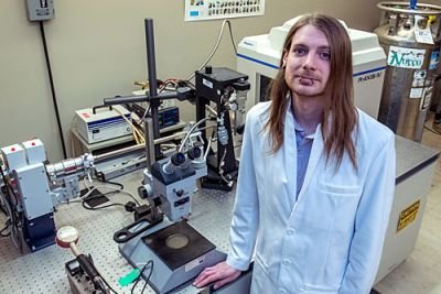 Sascha Stump poses for the camera while standing in his lab at UM