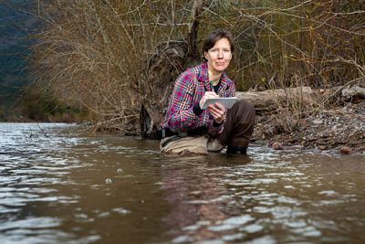 A picture of Claire Rawlings Gilder kneeling in a river with waders