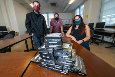 UM doctoral student Tre Bloom (left), acting CIO Zach Rossmiller (center) and Associate Professor Meradeth Snow pose with physical hard disks.