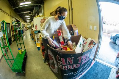 Molly Kirkham, an AmeriCorps team leader with the Missoula Food Bank, looks over some of the 672,000 pounds of food donations produced by Can the Cats.