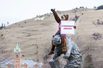 A picture of Monte the mascot on the Griz Statue holding a Congratulations Grads sign.