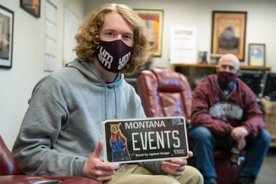 "UM student Jack Person holds a license plate that says ""Montana Events."""