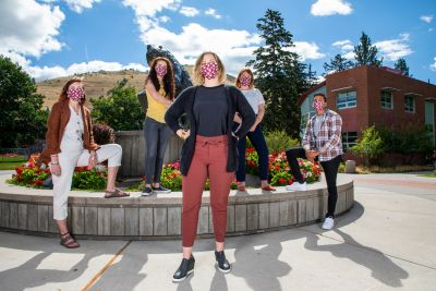 Five people stand in front of the Grizzly Bear statue in masks and the closest person has her hands on her hips