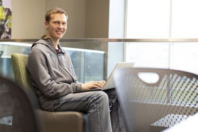 A UM student sits in front of a laptop computer on campus.