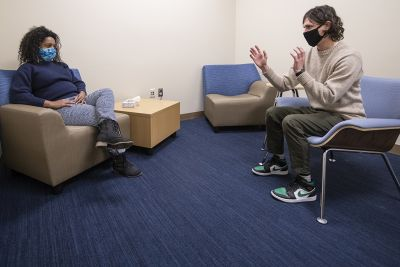 Two UM doctoral students sit and talk in one of UM's counseling rooms in the College of Education Building.