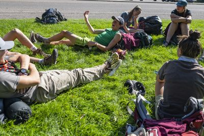 UM students sit on a green law on campus in a circle and talk