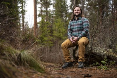 A UM student sits on a stump in the woods.
