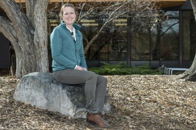 Hilary Martens, in a blue sweatshirt, sits on a rock