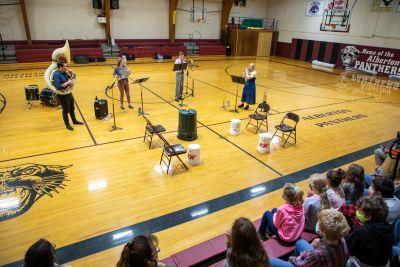 UM music alumni play instruments in a school gymnasium