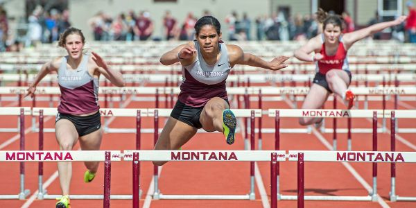 Student athlete jumping hurdles