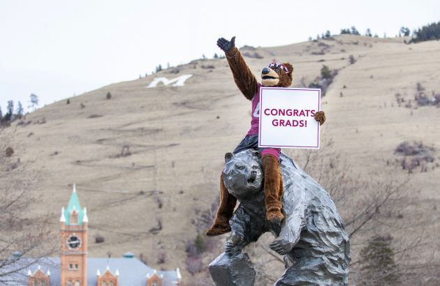 Monte sits atop the Grizzly statue holding a sign that reads: Congrats, grads!